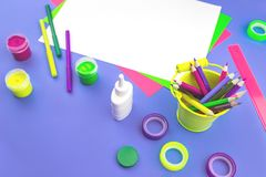 Bright violet desk with assorted neon stationery royalty free stock photo