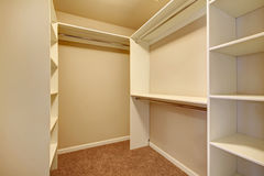 Bright walk-in closet. Ivory and beige walk-in closet with carpet floor royalty free stock photo