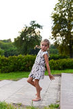 A little girl dancing and making funny faces on a grass in a beautiful green park. A bright warm positive photo of a little girl dancing and making funny faces Royalty Free Stock Photography