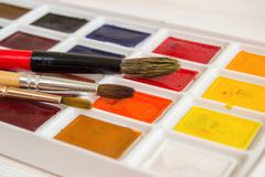 Bright watercolor paints close-up in a box with brushes royalty free stock images
