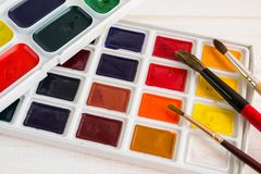 Bright watercolor in a white box with brushes stock image