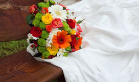 Bright wedding bouquet on white dress. The flowers are orange, red, white, green Royalty Free Stock Photo