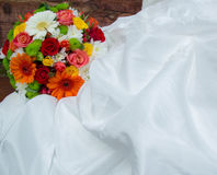 Bright wedding bouquet on white dress. The flowers are orange, red, white, green Stock Image