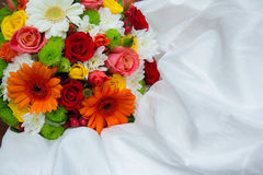 Bright wedding bouquet on white dress. The flowers are orange, red, white, green Royalty Free Stock Image