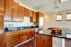 Bright whiskey color kitchen with black marble counter tops Royalty Free Stock Photo