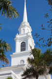 Bright white church steeple pierces the sky on clear day Royalty Free Stock Images
