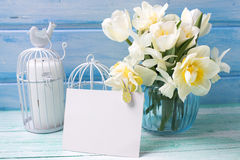 Bright white daffodils and tulips  flowers in blue vase, candles Stock Photos