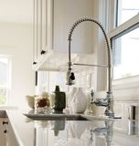Kitchen Faucet. White kitchen with carrara marble countertops and chrome faucet stock images