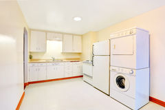 Bright white kitchen interior with laundry appliances Royalty Free Stock Photos