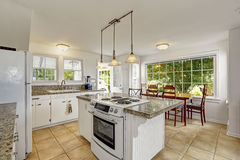 Bright white modern kitchen interior with island and dining area. White kitchen room with granite tops. Kitchen island with built-in stove. View of dining area Royalty Free Stock Image