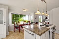Bright white modern kitchen interior with island and dining area Royalty Free Stock Photo