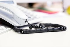 Bright white office telephone station on desk. Close up macro view, low angle perspective Stock Photos