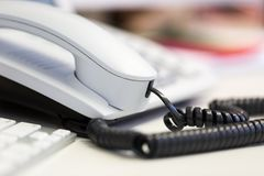Bright white office telephone station on desk. Close up macro view, low angle perspective Royalty Free Stock Photos