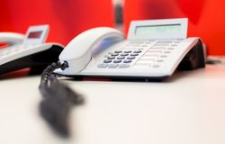 Bright white office telephone station on desk. Close up macro view, low angle perspective Stock Photo