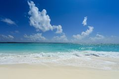 View of the Indian ocean. Bright white sand and gentle ocean waves under deep blue cloudy sky of Maldives Royalty Free Stock Image