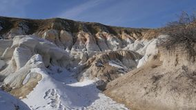 Bright white snow covers ground around interesting geologic site. White snow covers the sandy ground around the site of rounded white rock near cliff face royalty free stock image