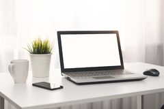 Bright white workplace with laptop on the table Royalty Free Stock Photography