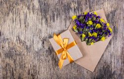 Bright wild flowers in a paper envelope and a gift with a golden ribbon on a worn wooden background. Backgrounds and textures. Bright wild flowers in a paper Stock Photos