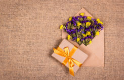 Bright wildflowers in an envelope and a gift box with a gold ribbon. Festive concept. Backgrounds and textures. Royalty Free Stock Photo
