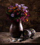 Bright wildflowers in vase and old coins Stock Photos