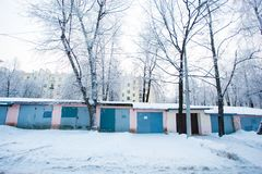 Winter morning. Chain of garages surrounded by snow piles stock photo