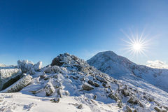 Bright winter scenery in the mountains, with frost and rocks covered with fresh snow. On a cold freezing day Royalty Free Stock Photo