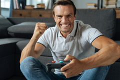 Bright witty guy winning another round. Home champion. Energetic ambitious enthusiastic man spending his weekend at home and enjoying his hobby while completing Stock Image