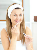 Bright woman applying gloss on her lips. In the bathroom at home Stock Photography