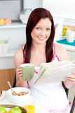 Bright woman eating cereals and reading newspaper. Bright woman eating cereals while reading newspaper in the kitchen at home Royalty Free Stock Image