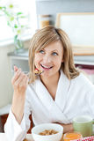Bright woman eating cereals wearing a bath robe Royalty Free Stock Images