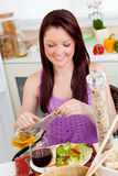 Bright woman eating a salad with oil at home Royalty Free Stock Photos