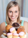 Bright woman holding a plate of cakes Royalty Free Stock Image
