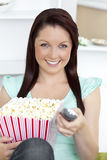 Bright woman holding a remote and popcorn Royalty Free Stock Photo