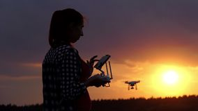 Bright woman holds a panel to operate her drone at sunset in slo-mo. An amazing view of a young woman who holds a panel with a screen to control her flying drone stock video footage