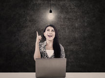 Bright woman with laptop and lit bulb Stock Photography