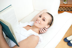 Bright woman reading a book lying on a sofa Royalty Free Stock Images