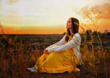 Bright woman relax sitting on a sunset field. Stock Photos
