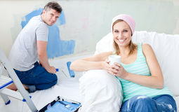Bright woman relaxing boyfriend paint the room. Bright woman relaxing on a sofa boyfriend paint the room Stock Photo