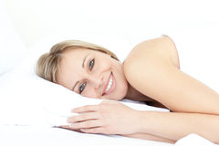 Bright woman relaxing on her bed Stock Images