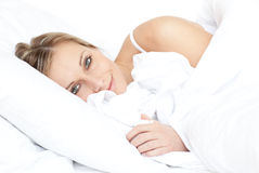 Bright woman relaxing lying on her bed stock image