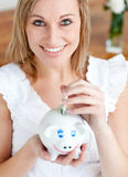 Bright woman saving money in a piggy-bank. At home Royalty Free Stock Images