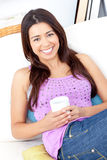 Bright woman smiling and holding a cup of coffee Stock Image
