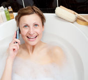 Bright woman talking on phone in a bubble bath Stock Images