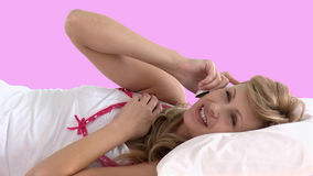 Bright woman talking on phone lying on a bed stock footage