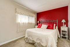 Bright woman& x27;s bedroom with red contrast wall Royalty Free Stock Image