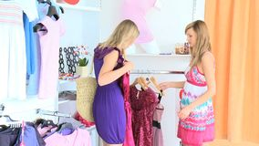 Bright women choosing dresses. In a clothes shop stock video footage