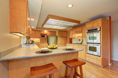 Bright wooden kitchen interior with steel appliances. Stock Photo
