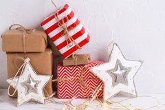 Bright wrapped gift boxes with presents, fairy lights  and decor. Ative  stars  on white textured background. Selective focus. Place for text Royalty Free Stock Photography