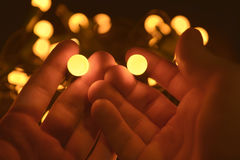 Bright yellow balls in the hands Royalty Free Stock Image