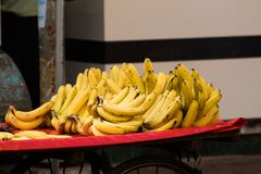 Bright yellow bananas being sold in colorful indian street food stock photo